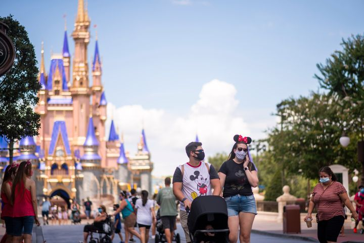Guests wear required face masks due to the Covid-19 pandemic on Main Street, U.S.A. in front of Cinderella Castle at Walt Dis