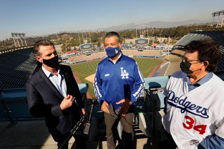 California Secretary of State Alex Padilla (center) celebrates the L.A. Dodgers' World Series win with Newsom (left). Padilla