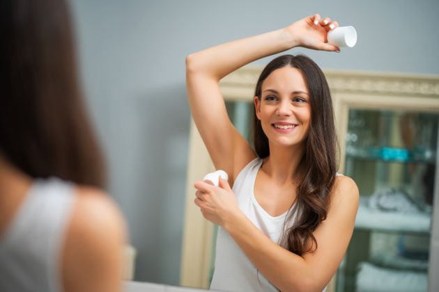 Portrait of young woman who is applying roller deodorant in her