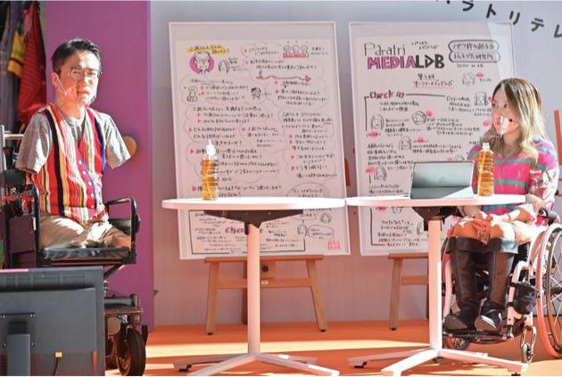 会場の横浜市役所につくられたステージにカラフルな衣装で登場した乙武洋匡さん(左)