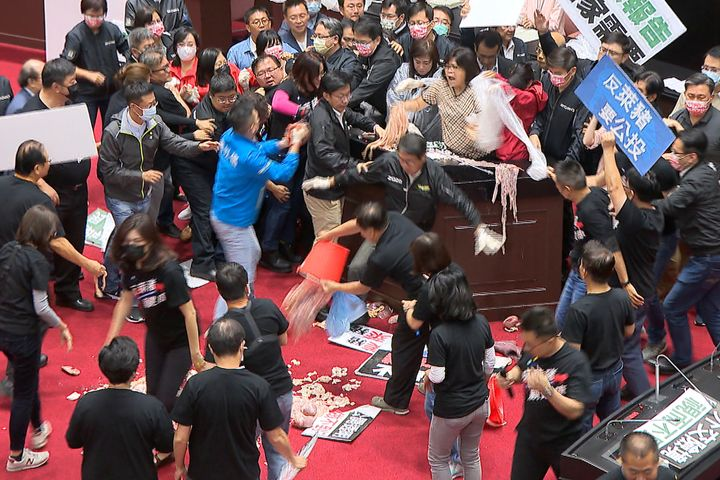 Taiwan's lawmakers got into a fist fight and threw pig guts at each other Friday over a soon-to-be enacted policy that would