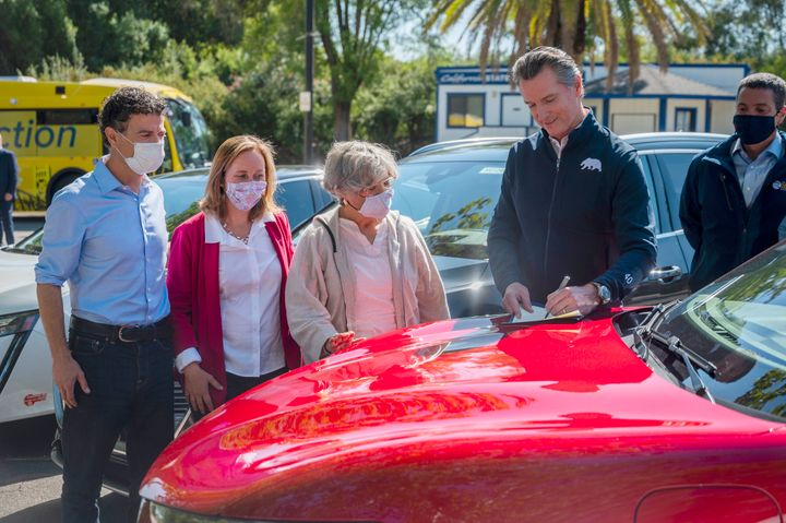 On the hood of an electric car, California Gov. Gavin Newsom signs an executive order requiring all new passenger vehicles so