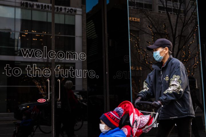 """A masked pedestrian passes a business with the words, """"Welcome to the future"""" on the front door on Nov. 20, 2020."""