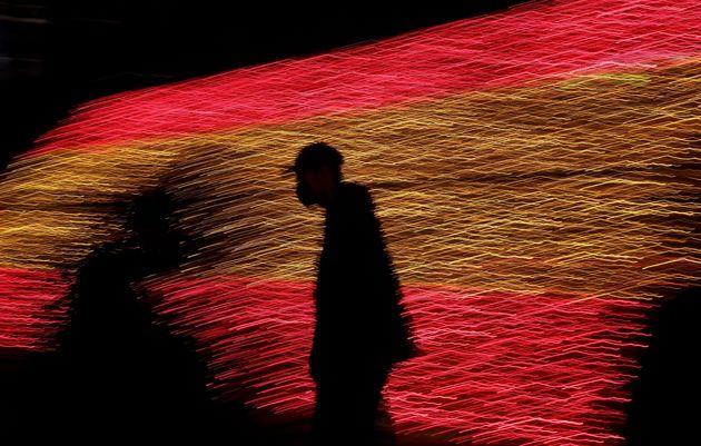 Un hombre camina el pasado 26 de noviembre en Madrid con las luces de Navidad que forman la bandera de