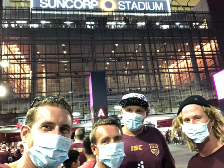 The writer and his mates don masks at the entrance of Suncorp Stadium in Brisbane.