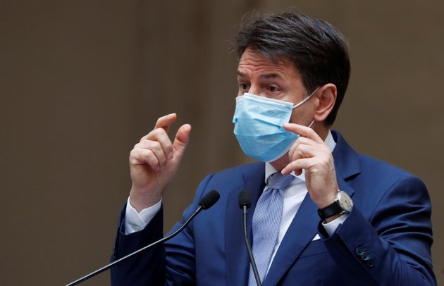 Italian Prime Minister Giuseppe Conte wearing a protective face mask gestures as he speaks during a news...