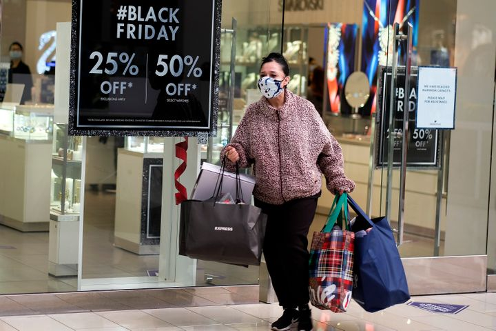 A Black Friday shopper wearing a face mask carries bags at the Glendale Galleria in Glendale, Calif., Friday, Nov. 27, 2020.