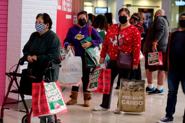 Black Friday shoppers wearing face masks wait in line to enter a store at the Glendale Galleria in Glendale,...