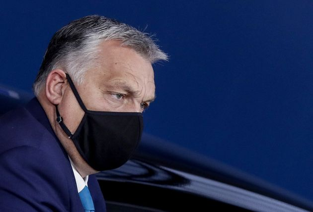 Hungarian Prime Minister Viktor Orban, wearing a face mask, arrives on the second day of a two days face-to-face...