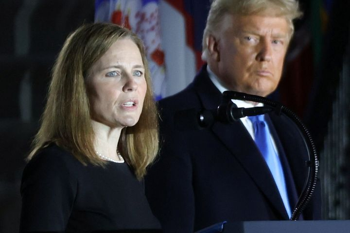 President Donald Trump looks on as Judge Amy Coney Barrett delivers remarks after she was sworn in as an associate justice of