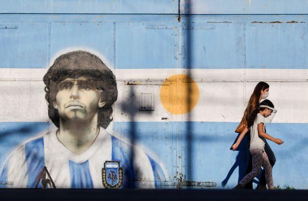 FILE PHOTO: People walk past a graffiti of soccer legend Diego Armando Maradona in Buenos Aires, Argentina,...