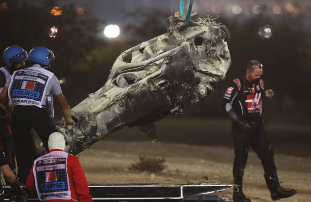 Track marshals clear the debris following the crash of Romain Grosjean of France and Haas F1 during the...