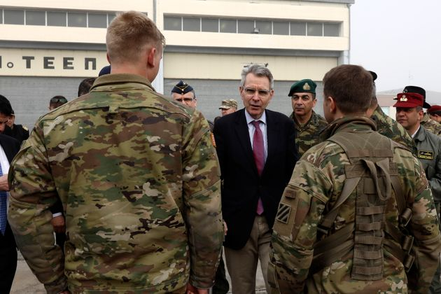 U.S. Ambassador Geoffrey Pyatt to Greece, center, speaks with U.S. soldiers at a military base in Stefanovikio, central Greece on Wednesday, Feb. 19, 2020. Army aviation forces from Greece and the United States are taking part in a live-fire exercise with attack helicopters, marking deepening defense ties between the two countries. (AP Photo/Yorgos Karahalis)