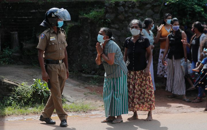 A family member of an inmate pleads to a police officer as she seeks information on the condition of her relative outside the