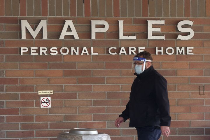 A man wearing a mask and face shield walks past the Maples Personal Care Home in Winnipeg, Man., on Nov. 2, 2020.