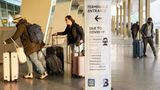 A sign displaying COVID-19 prevention protocols stands beside the passenger drop-off area as travelers arrive at Terminal C at LaGuardia Airport, Wednesday, Nov. 25, 2020, in the Queens borough of New York. Millions of Americans are taking to the skies and hitting the road ahead of Thanksgiving at the risk of pouring gasoline on the coronavirus fire. They are disregarding increasingly dire warnings that they stay home and limit their holiday gatherings to members of their own household. (AP Photo/John Minchillo)
