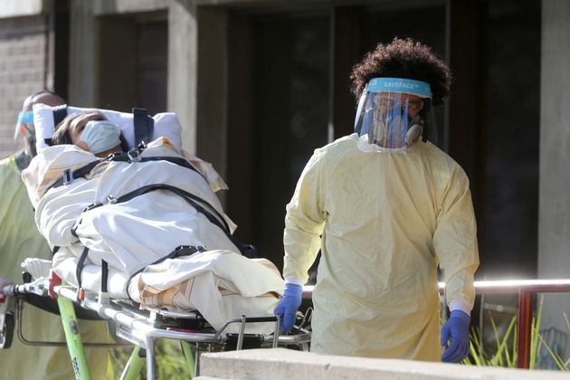 Employees of a stretcher service wear personal protective gear as they return a resident to Parkview...