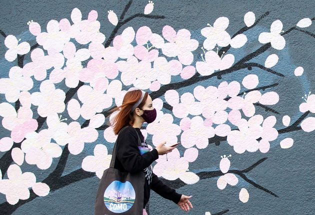 A woman wearing a face mask to prevent the spread of COVID-19 walks past a mural in Vancouver on Nov....