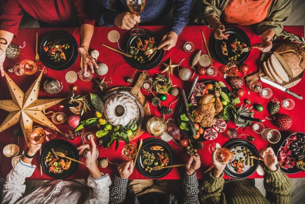 Friends celebrating Christmas. Flat-lay of people eating and talking over festive table with red cloth...