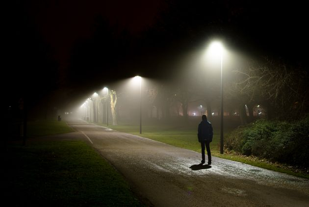 Single Person Walking on Street in the Dark