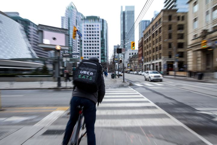 An Uber Eats food courrier on his bicycle in Toronto.