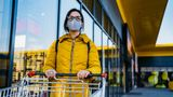 Young beautiful Caucasian woman with shopping cart in grocery store. Woman wearing a mask in time of pandemic of Coronavirus / Covid-19.