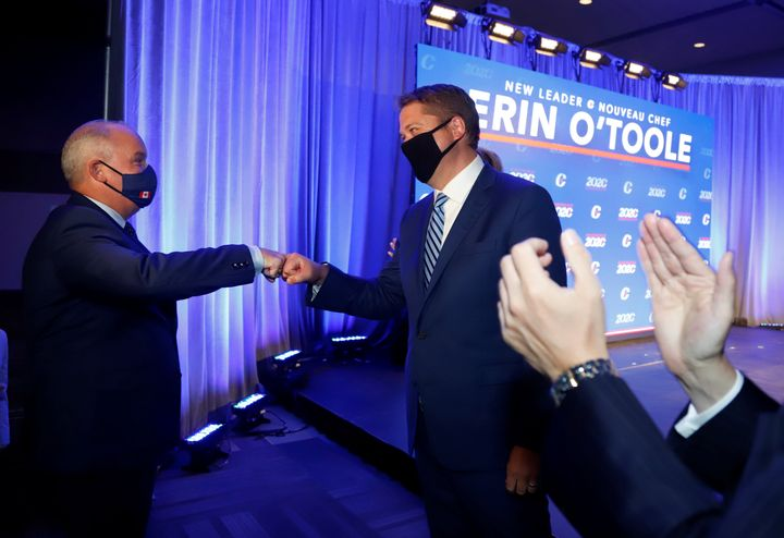 Erin O'Toole, the new leader of Canada's Conservative party, fist bumps outgoing leader Andrew Scheer before giving his victory speech in Ottawa, Aug. 24, 2020.
