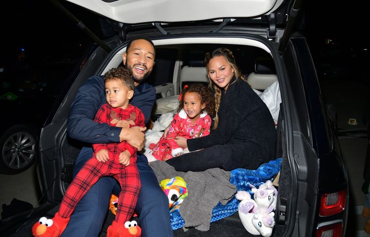 """John Legend and Chrissy Teigen are pictured with Miles and Lunaat Netflix's """"Jingle Jangle: A Christmas Journey"""" drive-in premiere on Nov. 13 in Los Angeles."""