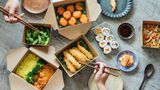 Flat lay of two people's hands using chopsticks while sharing assorted takeaway Asian food at the dining table.