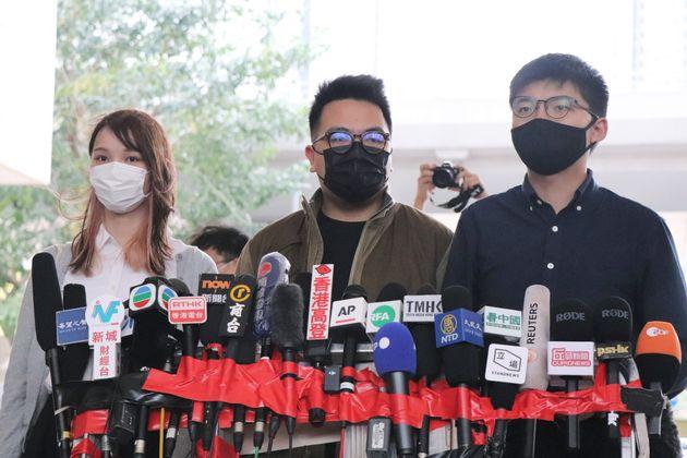 23日、香港の裁判所で記者団の取材に応じる(右から)黄之鋒、林朗彦、周庭の3氏