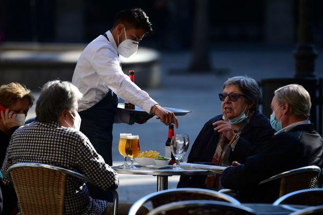 Un camarero sirve en una terraza de Barcelona en noviembre tras la reapertura dela