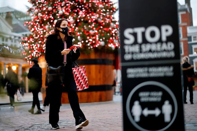 A pedestrian wearing a protective face covering walks past the Christmas tree in Covent Garden in central...