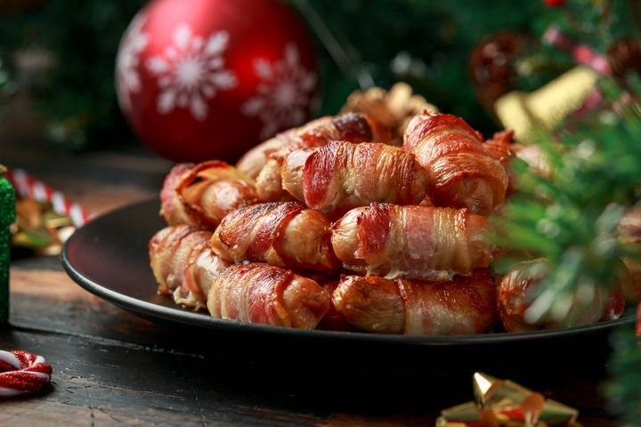 Christmas Pigs in blankets, sausages wrapped in bacon with decoration, gifts, green tree branch on wooden rustic table.