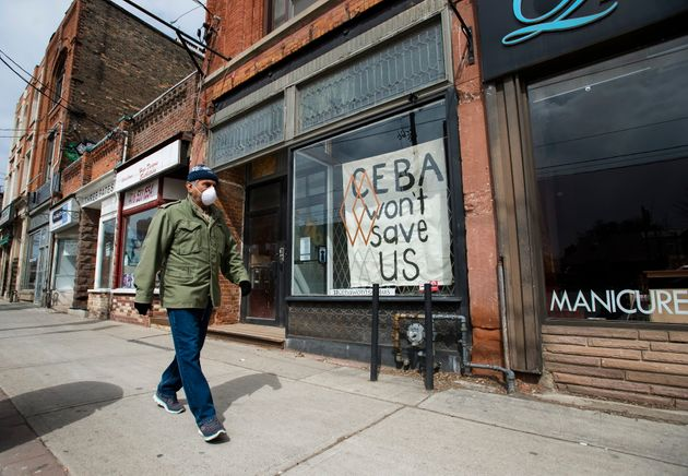A closed store front boutique business pleads for help displaying a sign in Toronto on Thursday, April...