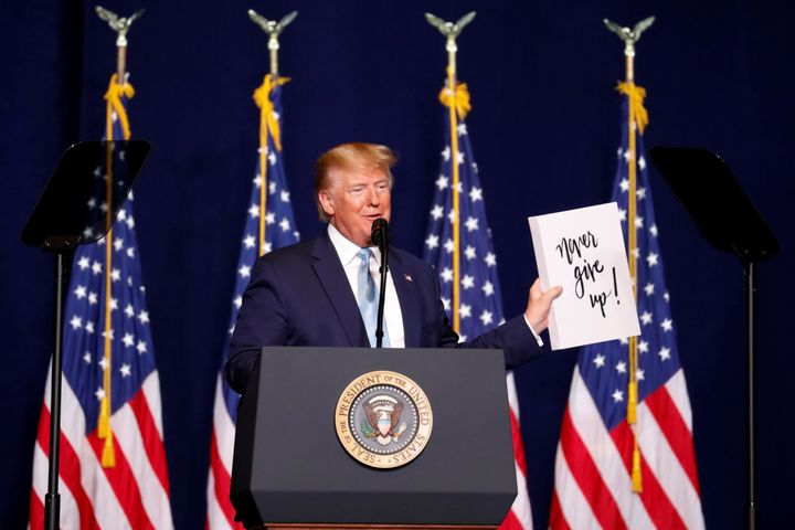 "Trump holds a sign that reads, ""Never give up!"" as he speaks to evangelical supporters in Miami on Jan. 3, 2020."