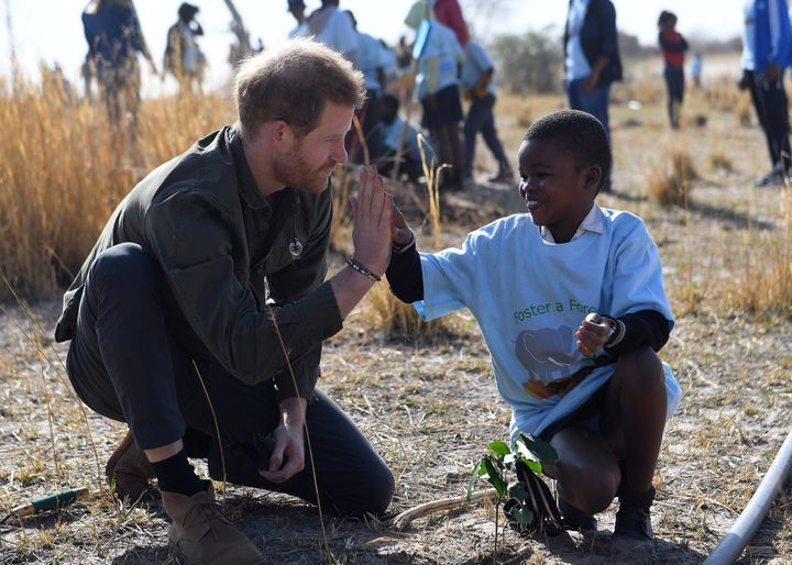 Prince Harry helps young students plant trees at the Chobe Tree Reserve in Northern Botswana on Sept. 26, 2019.