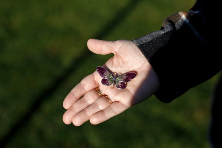 Kara Ferreira holds a butterfly brooch like the one buried with her mother Elise Arthur, whom she lost to COVID-19 as the first wave ripped through long-term care homes in Ontario.