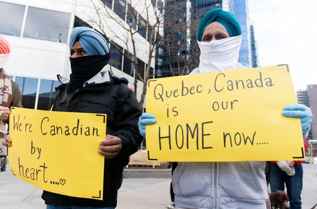 People take part in a demonstration outside Quebec Premier Francois Legault's office in Montreal on Nov....
