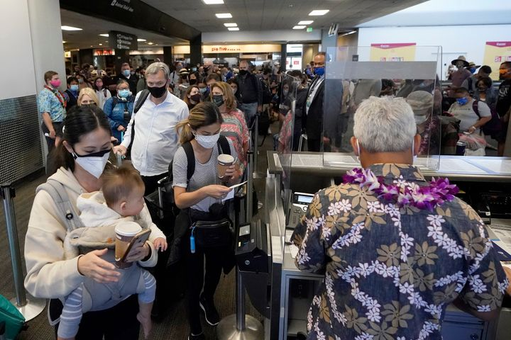United Airlines passengers walk through the gate to board an Oct. 15 flight to Hawaii at San Francisco International Airport.