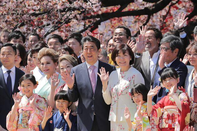 「桜を見る会」で招待客と記念撮影する安倍晋三前首相(中央)=2019年4月、東京・新宿御苑