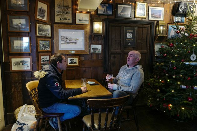 Customers enjoy their drinks next to a Christmas tree at the Chainlocker pub on December 2, 2020 in Falmouth,...