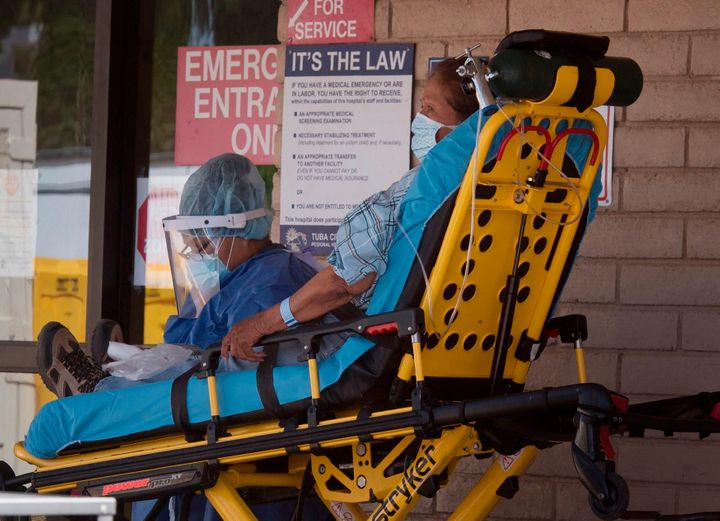 A patient is taken from an ambulance into a hospital in the Navajo Nation town of Tuba City during a 57-hour curfew, imposed to try to stop the spread of the COVID-19 virus, on May 24, 2020.