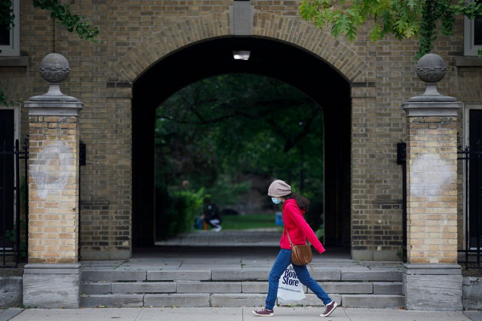 A person carrying a University of Toronto book store shopping bag walks on the university's campus in...
