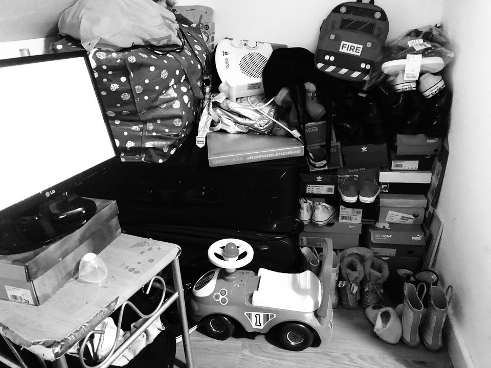 Belongings stuffed under the eaves in Rafiat's small room. The ceiling is so low, she has to sit on the...