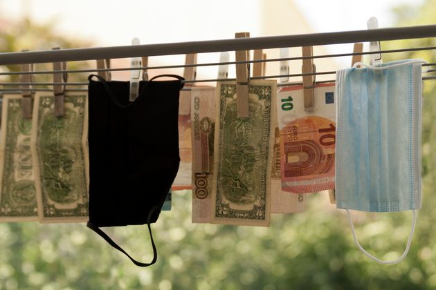 Money laundering concept: Face masks hanging out to dry on clotheslines among dollar, euro and Russian...