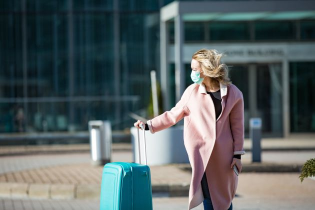 Woman in protective mask standing at airport entrance with smartphone and big luggage case, browsing,...