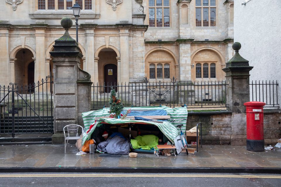 Two homeless men sleeping under a makeshift tent with festive decorations in Oxford,