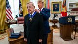 WASHINGTON, DC - DECEMBER 03: President Donald Trump presents the Medal of Freedom to former college football coach Lou Holtz in the Oval Office of the White House on December 3, 2020 in Washington, DC. Holtz is best known for his time as head coach of University of Notre Dame's football team, winning a national championship in the 1988 season. (Photo by Doug Mills-Pool/Getty Images)