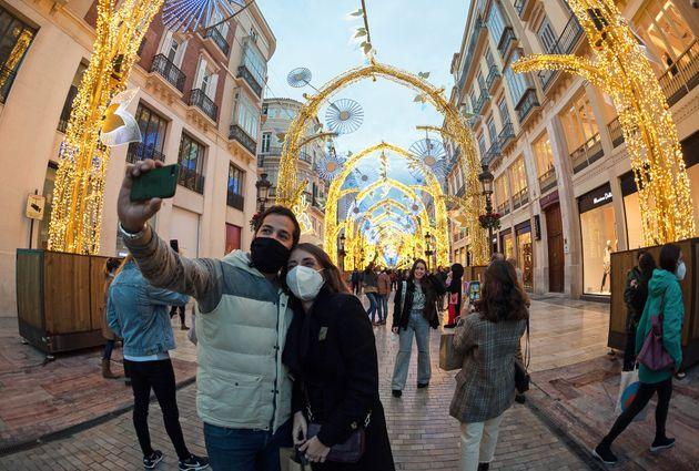 Una pareja se hace un selfi en la calle Marqués de Larios de