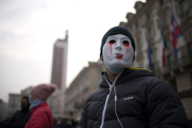 TURIN, ITALY - NOVEMBER 15: A man wearing a mask attends the protests organized by commerciants and citizens...